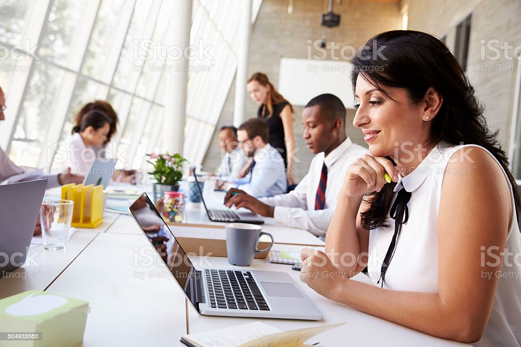 Businesswoman Working On Laptop In Busy Office stock photo