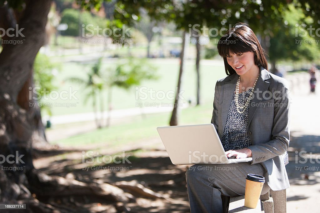 Businesswoman working on laptop in park royalty-free stock photo
