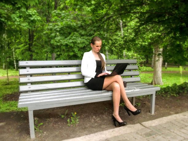 Businesswoman working on laptop sitting on a bench in the park stock photo