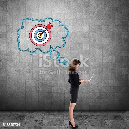 istock Businesswoman working on laptop with dartboard on wall 618355734