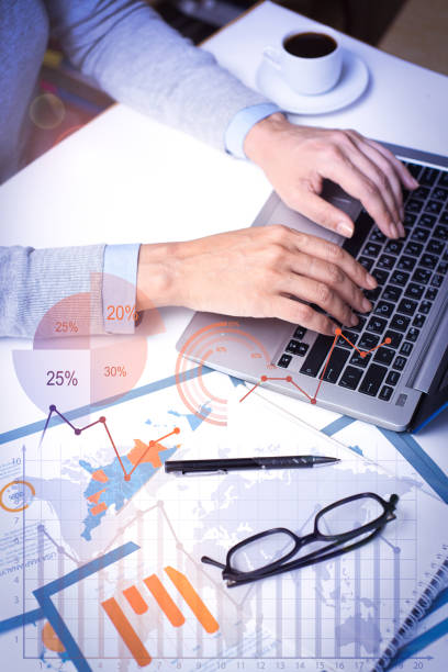 Businesswoman working on laptop with financial analysis graphs stock photo