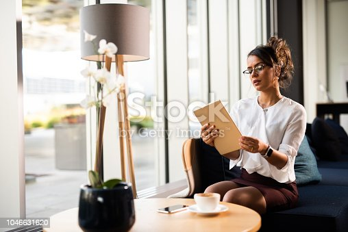 912944158istockphoto Businesswoman working on iPad. 1046631620