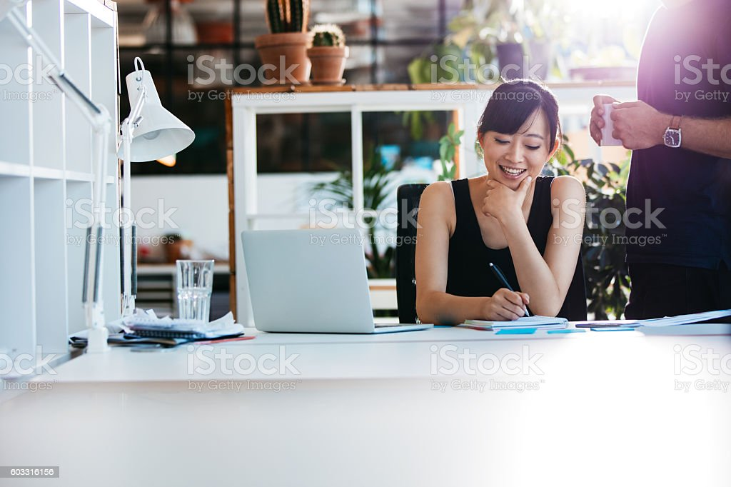 Businesswoman working with colleague standing by圖像檔