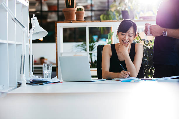 Businesswoman working with colleague standing by stock photo