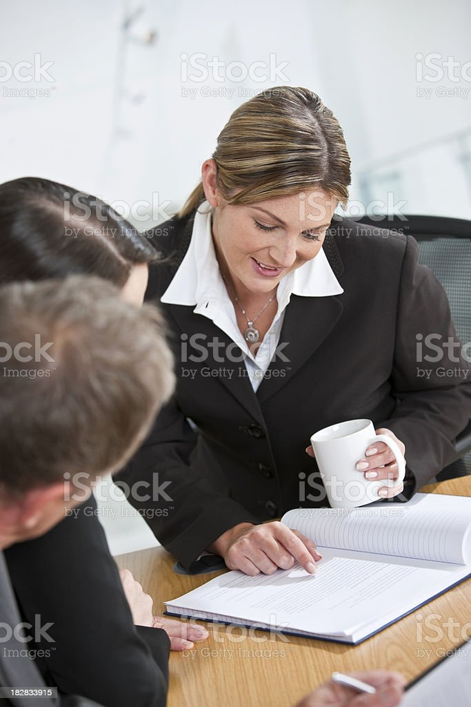 Businesswoman working with colleagues in office stock photo