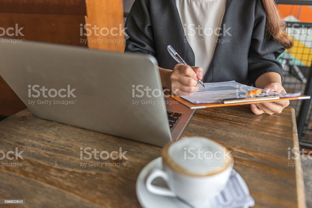 Businesswoman working with laptop, cappuccino and document stock photo