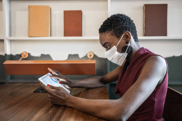 businesswoman working with mask using digital tablet at work - afro latino mask imagens e fotografias de stock