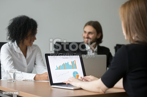 istock Businesswoman working with project statistics preparing report at team meeting 958531396