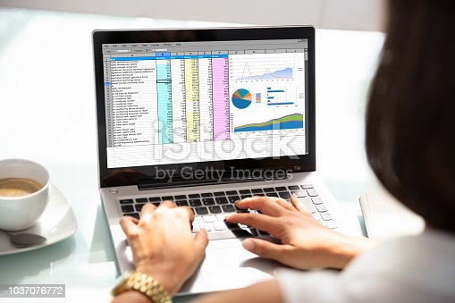 Close-up Of A Businesswoman's Hand Examining Spreadsheet On Laptop In Office
