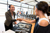 Cheerful mid adult businesswoman shakes hands with a colleague during a conference. The businesswoman is working at the conference registration table.