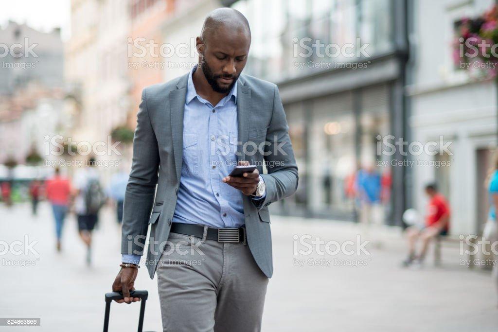 Eine Geschäftsfrau schreibt eine Nachricht auf einem Smartphone während des Gehens – Foto