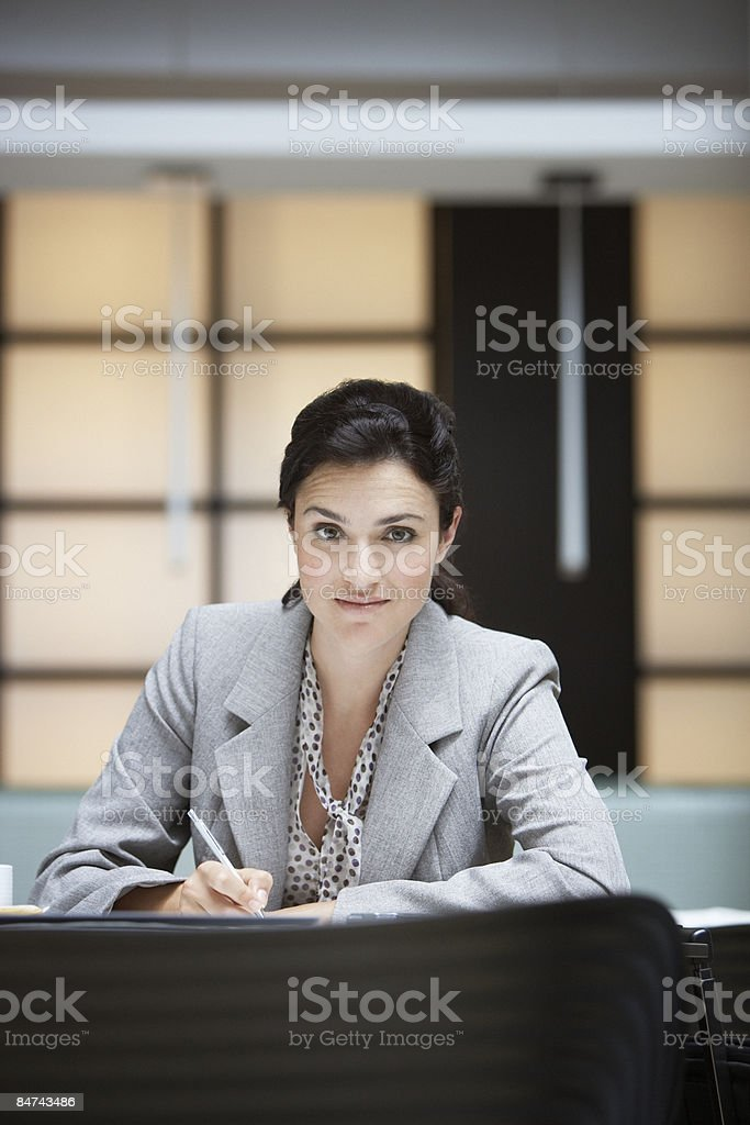 Businesswoman writing at office desk royalty-free stock photo