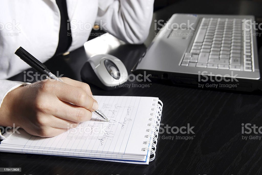 Businesswoman writing daily plan stock photo