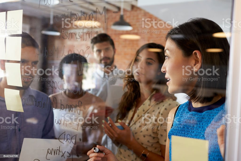 Businesswoman Writing Ideas On Glass Screen During Meeting stock photo