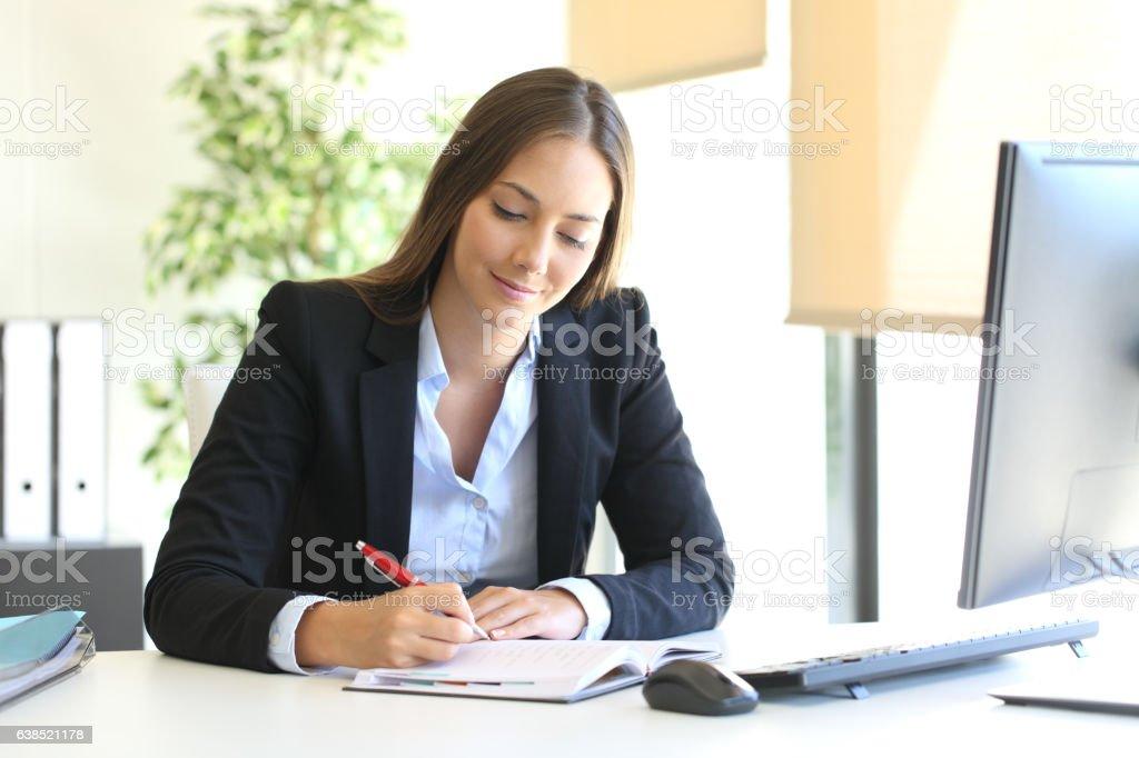 Businesswoman writing in an agenda at office Lizenzfreies stock-foto