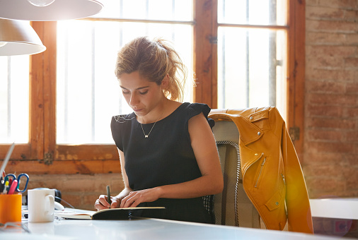 Young businesswoman writing in book at desk. Female professional is sitting on chair. She is making notes in office.