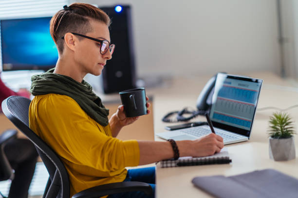 Geschäftsfrau schreibt Notizen im Büro und trinkt Kaffee – Foto