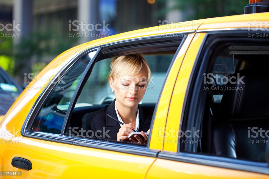 Businesswoman writing notes in yellow cab taxi stock photo