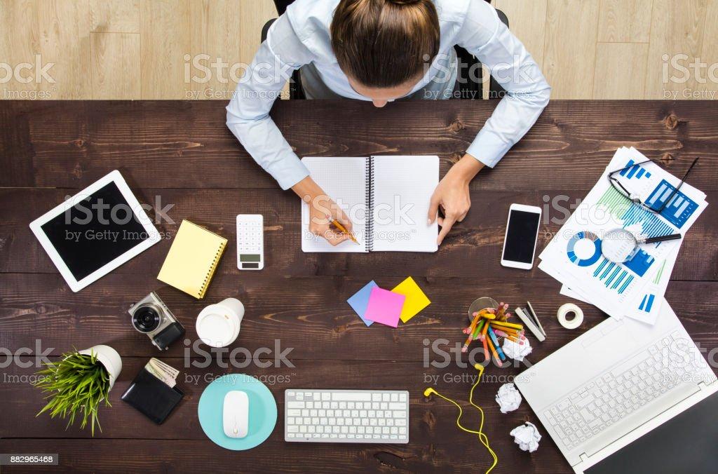 Geschäftsfrau, die auf ein leeres Notizbuch schreiben – Foto