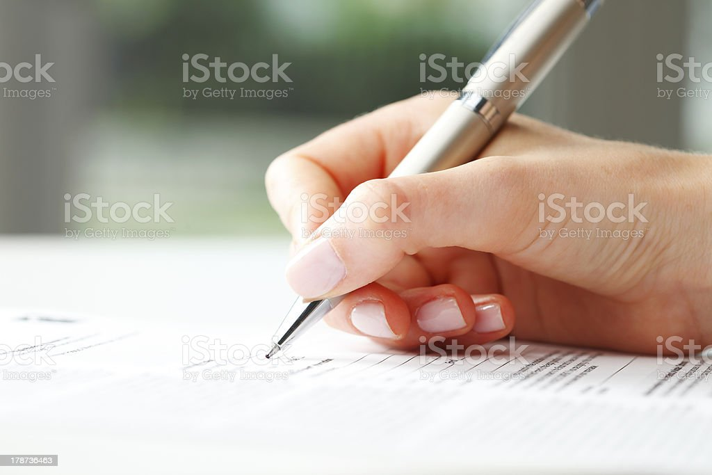 Businesswoman writing on a form stock photo
