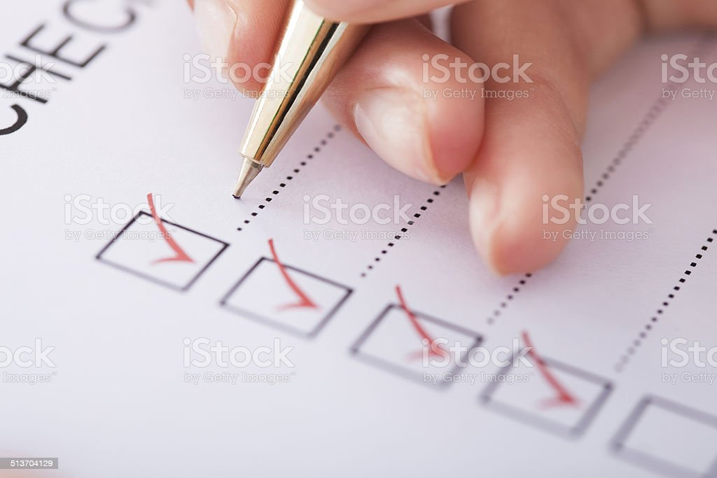 Businesswoman Writing On Checklist stock photo