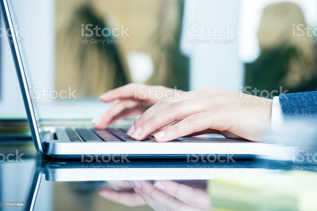 Businesswoman writing on laptop in her office royalty-free stock photo