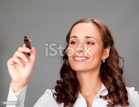 Happy smiling cheerful young business woman writing or drawing something on screen with red marker, over gray background