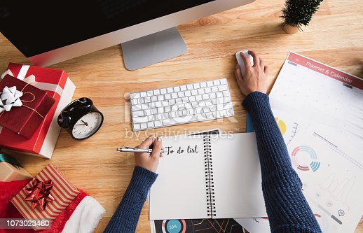 1073023470 istock photo Businesswoman writing to do list in christmas holiday at the office with christmas decoration on table. 1073023480