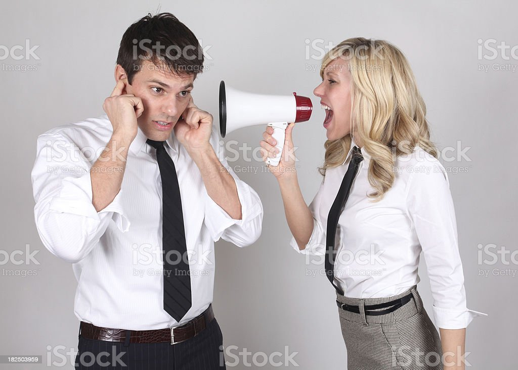 Businesswoman yelling at businessman with megaphone stock photo