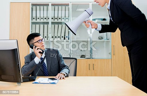 463813207 istock photo Businesswoman yelling at colleague through a bullhorn 507515884