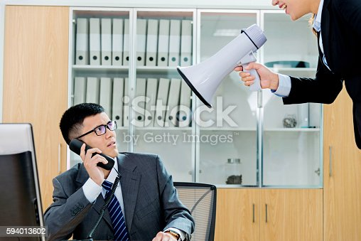 463813207 istock photo Businesswoman yelling at colleague through a bullhorn 594013602