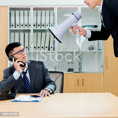 463813207 istock photo Businesswoman yelling at colleague through a bullhorn 638156292