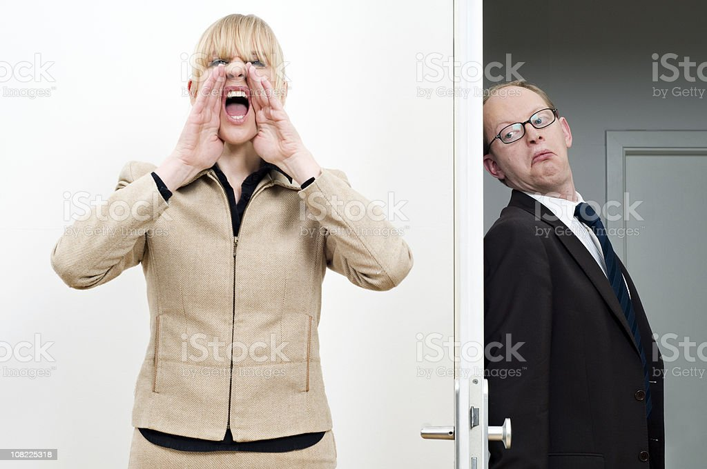 Businesswoman Yelling For Hiding Businessman royalty-free stock photo