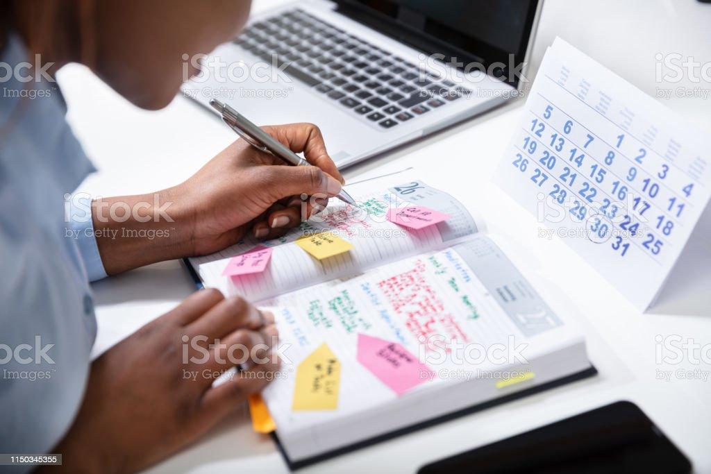 L'horaire de vérification de main de femme d'affaires dans l'Agenda - Photo de Affaires libre de droits