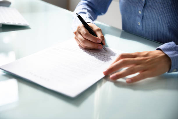Businesswoman's Hand Signing Contract Businesswoman's Hand Signing Contract With Pen Over Desk agreement stock pictures, royalty-free photos & images