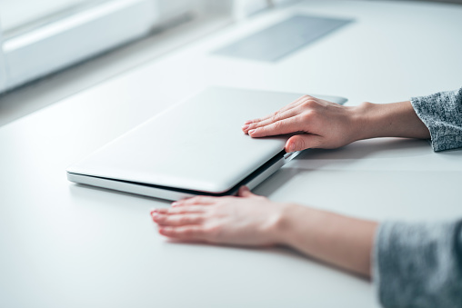 Businesswoman's hands closing or opening laptop on white table in bright office.