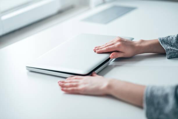 Las manos de la empresaria cerrando o abriendo el ordenador portátil sobre la mesa blanca en la oficina brillante. - foto de stock