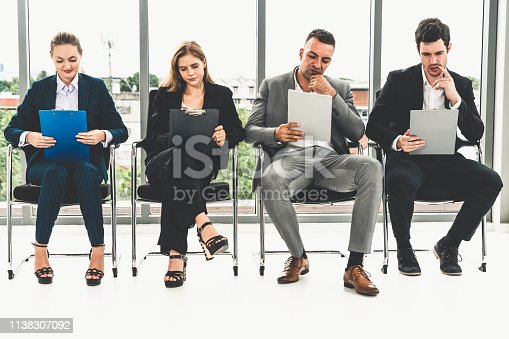587228412istockphoto Businesswomen and businessmen holding resume CV folder while waiting on chairs in office for job interview. Corporate business and human resources concept. 1138307092