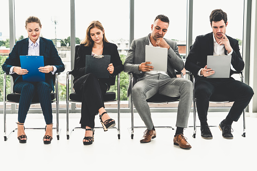 587228412 istock photo Businesswomen and businessmen holding resume CV folder while waiting on chairs in office for job interview. Corporate business and human resources concept. 1138307092