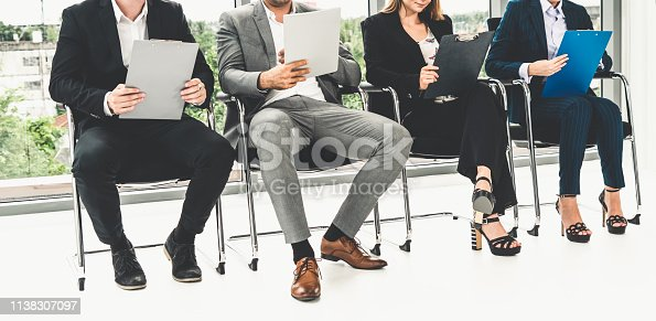 587228412istockphoto Businesswomen and businessmen holding resume CV folder while waiting on chairs in office for job interview. Corporate business and human resources concept. 1138307097
