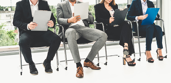 587228412 istock photo Businesswomen and businessmen holding resume CV folder while waiting on chairs in office for job interview. Corporate business and human resources concept. 1138307097