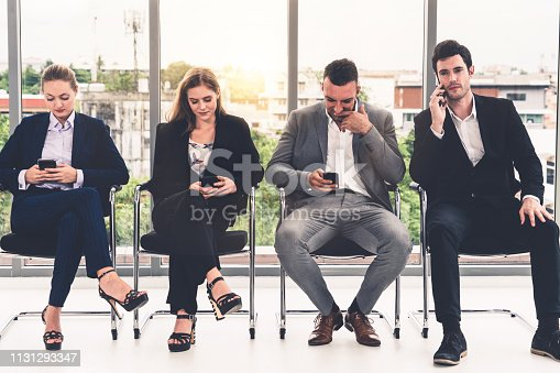 587228412istockphoto Businesswomen and businessmen using mobile phone. 1131293347