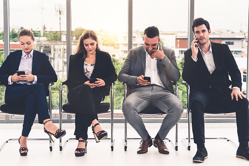 587228412 istock photo Businesswomen and businessmen using mobile phone. 1131293347