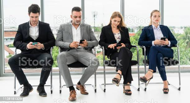 Businesswomen and businessmen using mobile phone while waiting on in picture id1128181329?b=1&k=6&m=1128181329&s=612x612&h=ypjtwruwwsgd7vhy pgxpgwyyrgvx0p1infpk3gtszg=