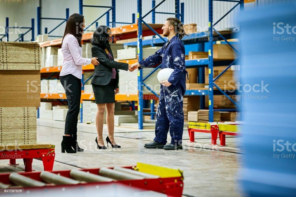 Businesswomen appreciating factory worker stock photo