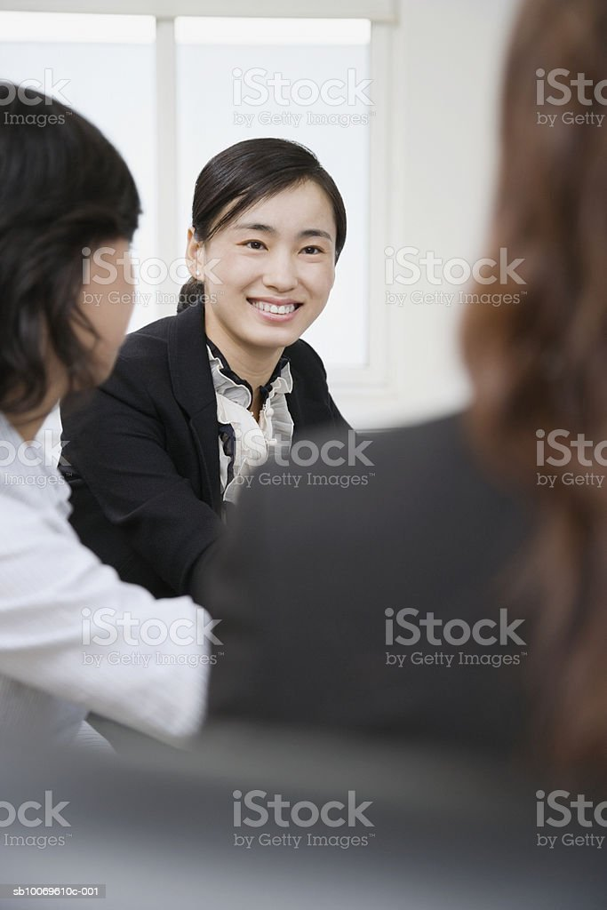 Businesswomen at conference room, focus on women in background royalty-free stock photo