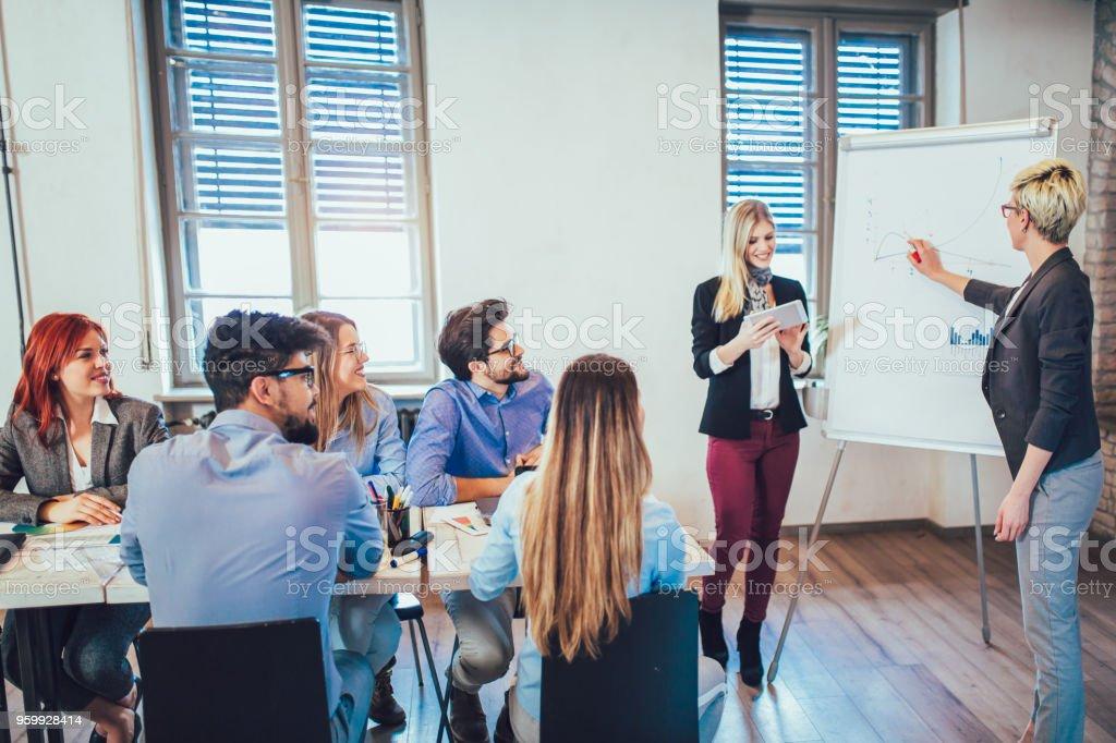 Mujeres empresarias en pizarra, presentación en la sala de juntas - foto de stock