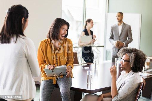 Diverse businesswomen brainstorm ideas together after meeting.