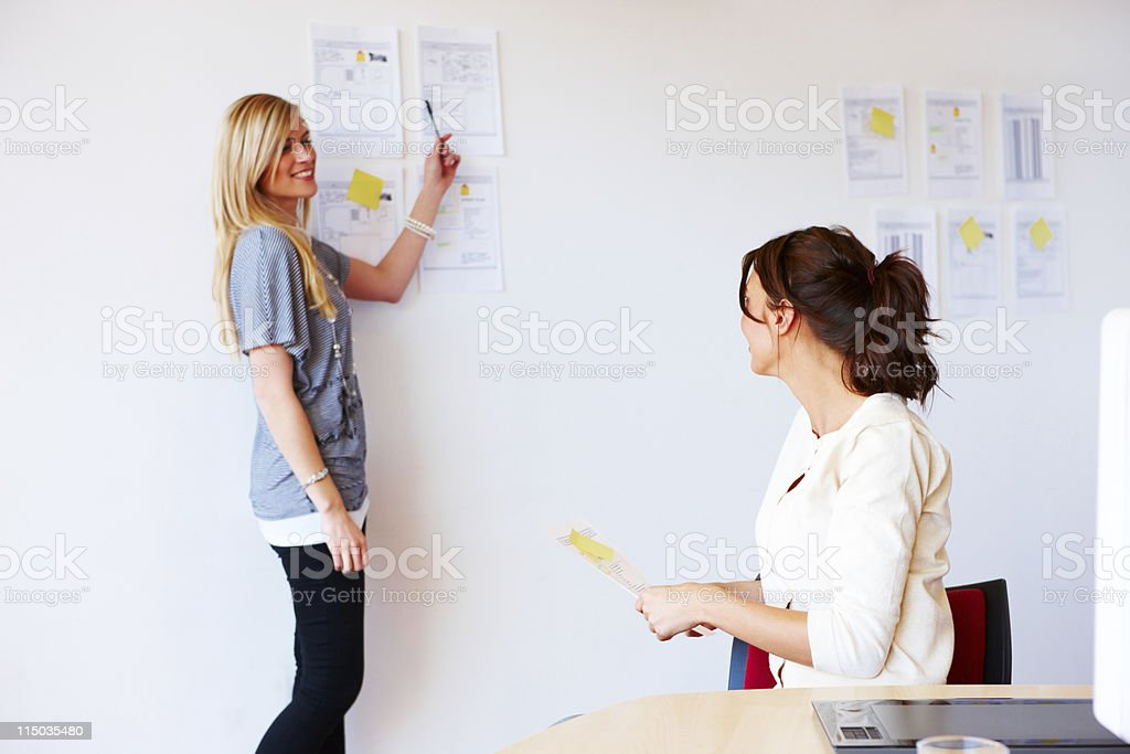 Businesswomen Discussing Documents On a Wall royalty-free stock photo