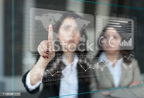 istock Businesswomen discussing financial dashboard on Projection Screen 1135381222